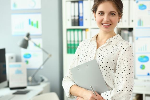 Красивая усмехаясь женщина стоя в офисе держа документ закрепленный к пусковой площадке