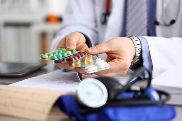 Гп в клинике, держа пачку разных волдырей крупным планом. практика прописывания жизненно важных лекарств и концепция юридической аптеки