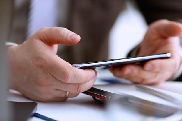 Мужская рука в костюме держит телефон и серебряную ручку