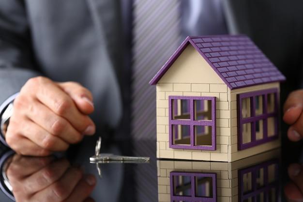 Мужчина в костюме и галстуке держит в руке серебряный ключ