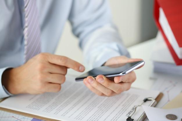 ビジネスマンが新しいスマートフォンを持っています