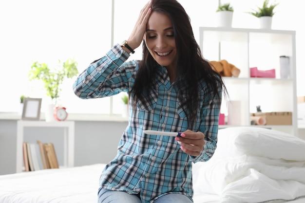 Молодая женщина смотрит на тест на беременность и радуется