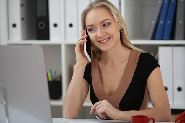 Блондинка деловая женщина разговаривает по телефону в офисе и улыбается