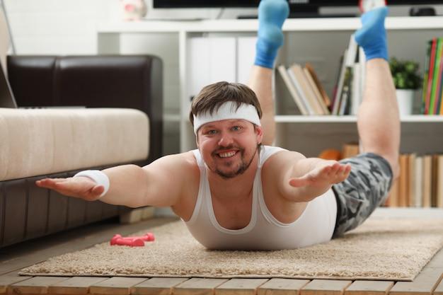 若いフィットネス男は脂肪マットの上にあります。