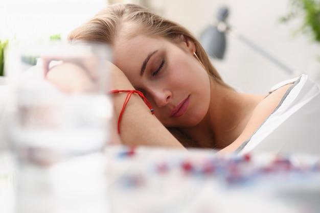 女性は病気で薬をベッドで寝る