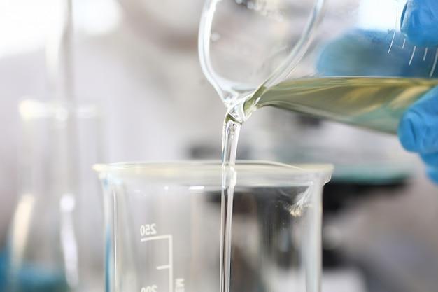 実験室のフラスコで黄色の液体を注ぐ青い保護手袋を身に着けている科学者の腕