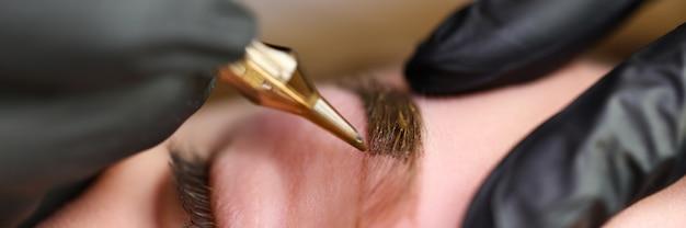 Крупный план профессионального визажиста, используя золотой инструмент и применяя цвет на форму бровей. макро съемка специалистов руки в защитные перчатки. концепция красоты и постоянной процедуры