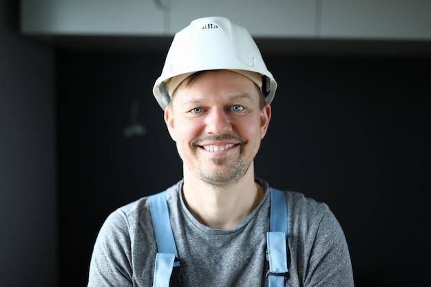 笑顔の保護用のヘルメットで作業服の男