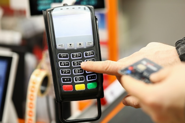 Крупный план лица, нажимающего ручки на терминале. оплата с использованием современного метода и пластиковой кредитной карты. расплачиваться в супермаркете или кафе. концепция технологий и инноваций