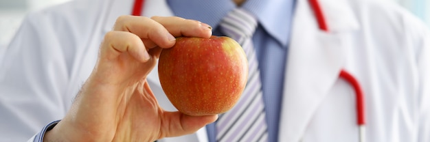男性医学治療学者医師の手が赤い新鮮な熟したリンゴを保持しています。医療支援または保険の概念。健康生活と健康的な食品のコンセプト。ベジタリアンライフスタイルのコンセプトです。果物とビタミン