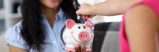 ピンクの面白い貯金箱を保持している幸せな母の肖像画。小さな子供がリサイクルボックスにお金を入れます。ママは幸せで娘を見ています。お金の節約のコンセプト