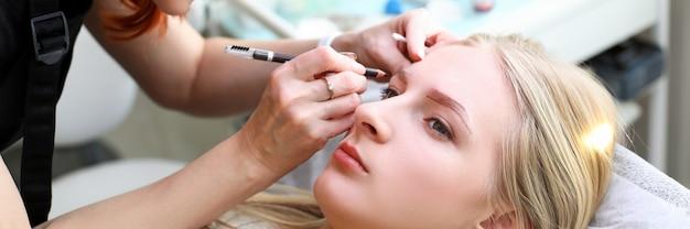 Косметолог строит натуральную форму брови девушки-клиента. татуаж бровей выполняется с помощью перманентного макияжа. эффект после микроблейдинга. несмываемый макияж. поездка в салон красоты для коррекции