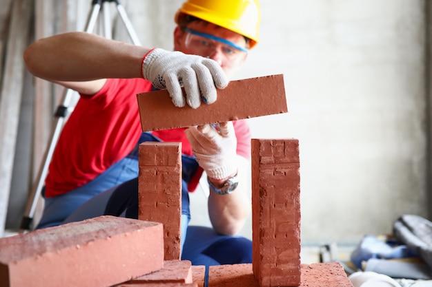 Мужчина строит кирпичную стену
