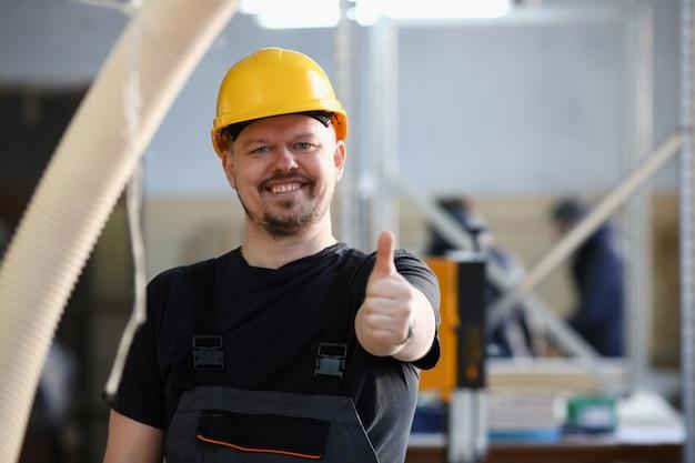 Усмехаясь работник в желтом шоу шлема подтверждает знак