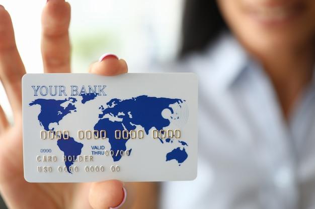 Женщина рука держит банковскую карту, показывая его