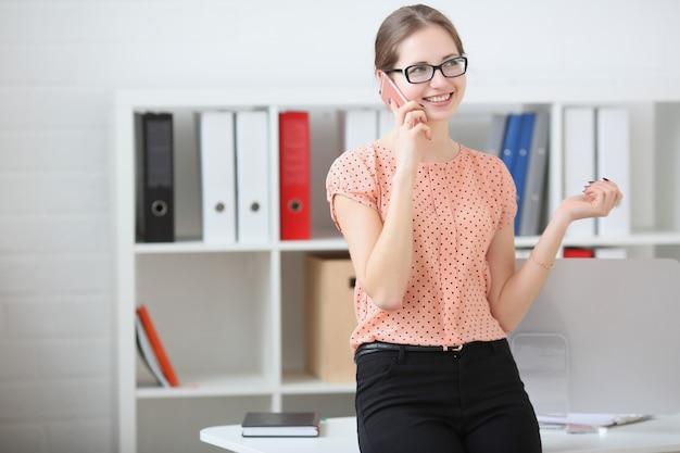 Деловая женщина разговаривает по телефону в офисе