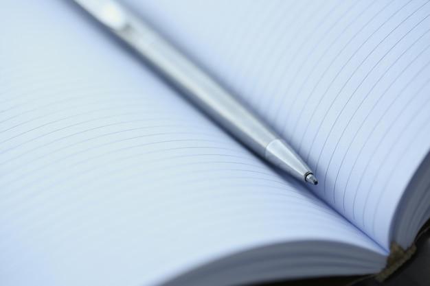 Серебряная ручка лежит на раскрытой тетради