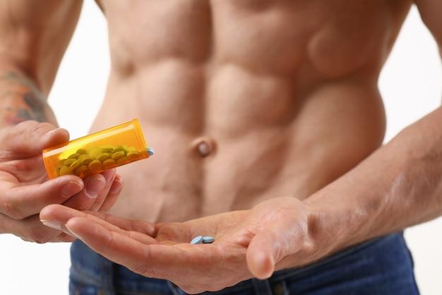 フィットネス男が瓶から錠剤をホルモンの彼の手の摂取量に注ぐ