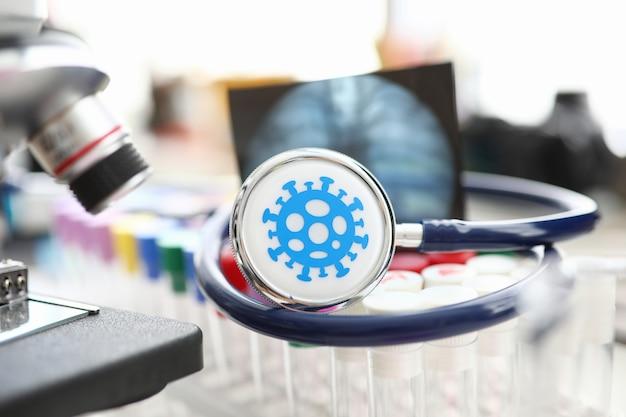 科学的な研究室のクローズアップでバイアルのセットの上に横たわる医療聴診器。ワクチン開発と薬物問題の概念