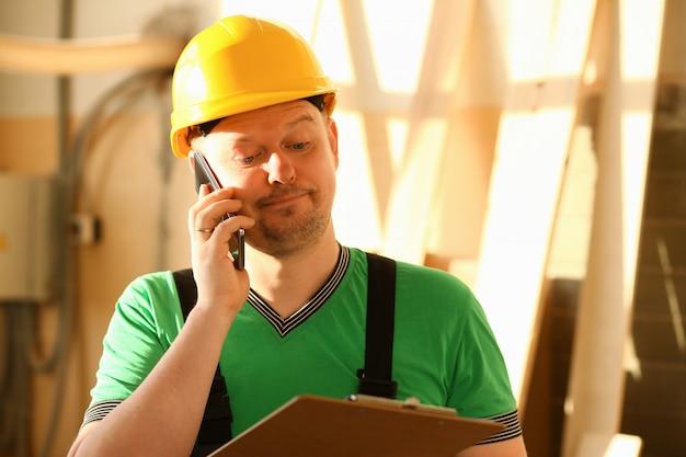 ハードウェアストアで電話で話している大工