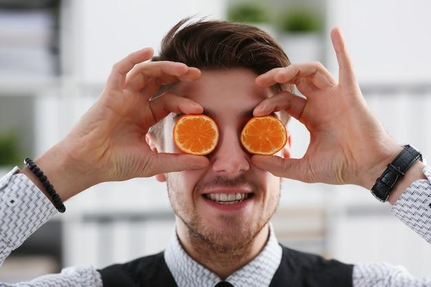 男性の手が目の高さでカットフルーツを保持