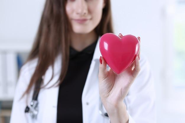赤いハートを保持している女性医学博士手