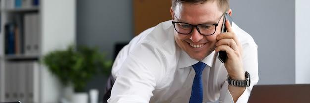 オフィスでうれしそうな男はノートパソコンの近くの電話で話します。金融システム会社を強化するための導入手法。男は隔離中に自宅からリモートで作業します。仕事を一新するスペシャリスト