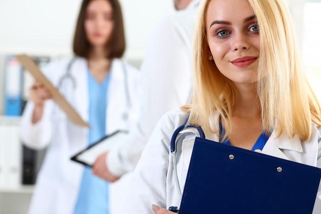 美しい笑顔の女性医師を保持し、クリップボードパッドを抱擁