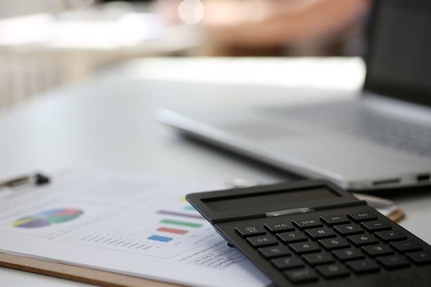 Черный калькулятор и финансовая статистика на планшете