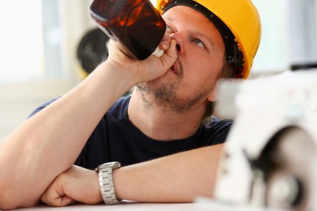 Рука пьяного работника в желтом шлеме