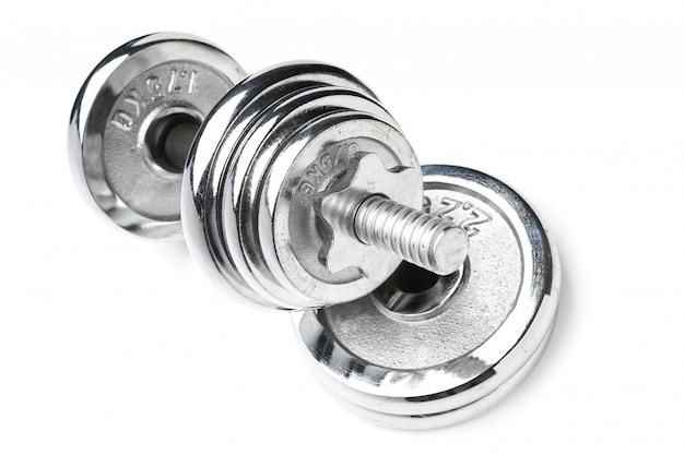 Серебристого цвета блестящая металлическая гантель стоит у стопки дисков