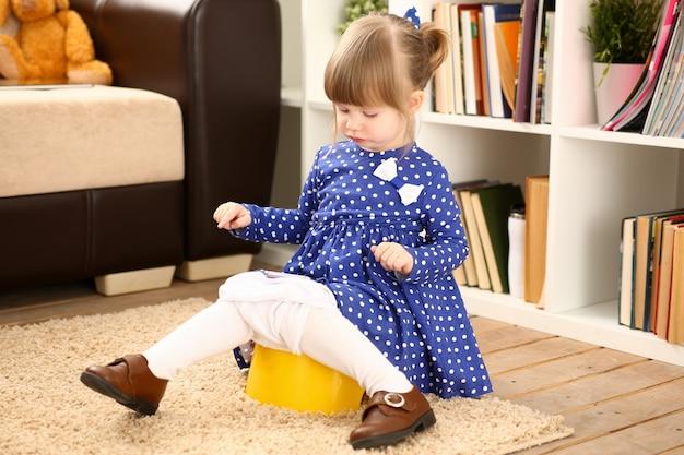 Милая маленькая женщина сидит на ее горшок
