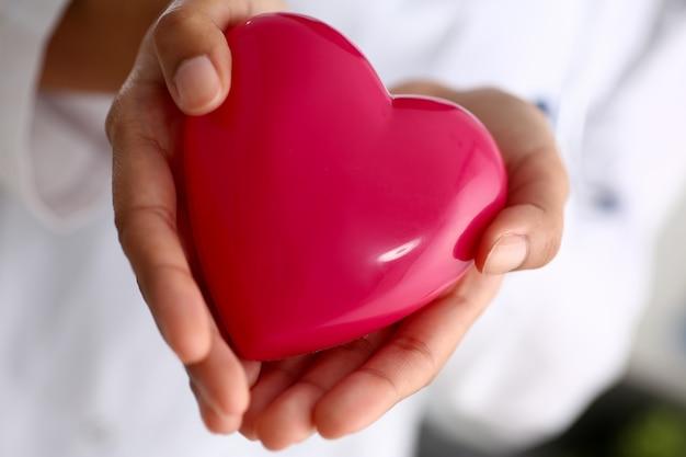 Женский доктор держит игрушку сердце