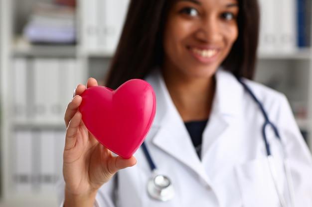 Красивая черная улыбающаяся женщина-врач держит игрушечное сердце