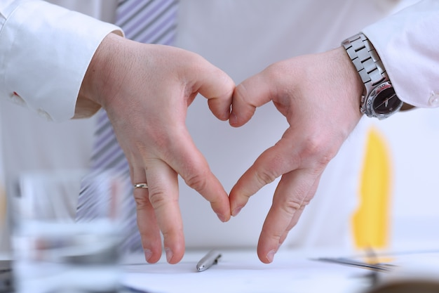 Мужские руки делают жест сердца