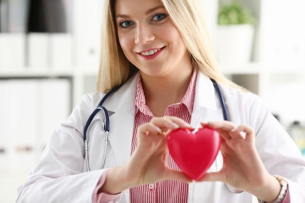 Красивое усмехаясь белокурое женское удерживание доктора