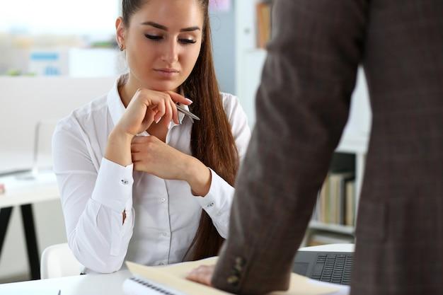 忙しいビジネスの女性に書類のパックを示す男性労働者