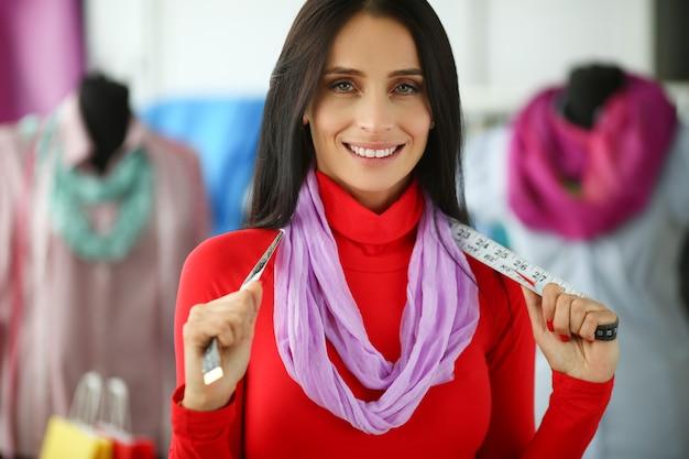 Стильная женщина модельер держит измерительную ленту