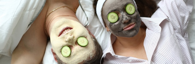 Пара лежит на кровати с косметическими масками на лице