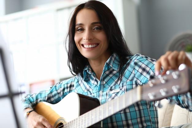Брюнетка играет на гитаре
