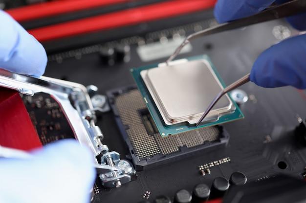 Мужская рука в синих защитных перчатках держит процессор