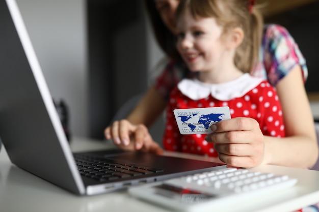 母と幸せな子供はプラスチック製のクレジットカードを手に保持