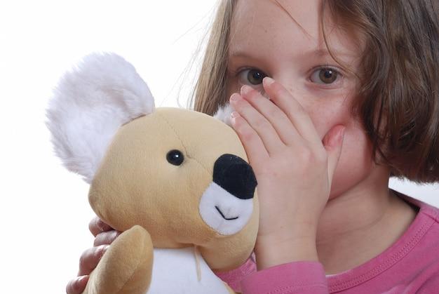 Молодая девушка обнимаются плюшевый мишка