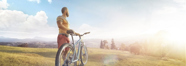 Велоспорт человек с велосипедом на лесной дороге в горах в летний день. горная долина во время восхода солнца.