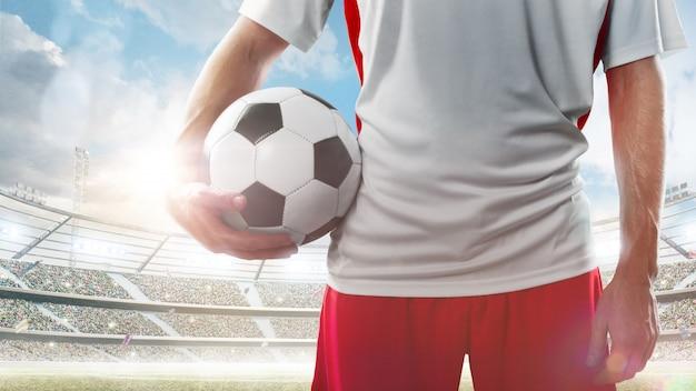 サッカーをクローズアップ。スタジアムでサッカーボールを保持しているプロのサッカー選手。