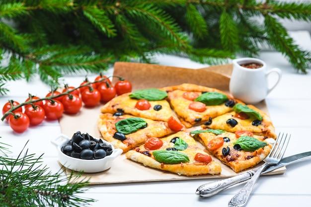白い背景とクリスマスのモミの枝にほうれん草とトマトのピザ