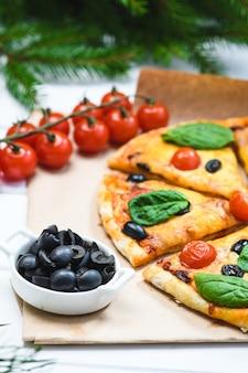 トマトとほうれん草の白い背景とクリスマスのモミの枝のピザ