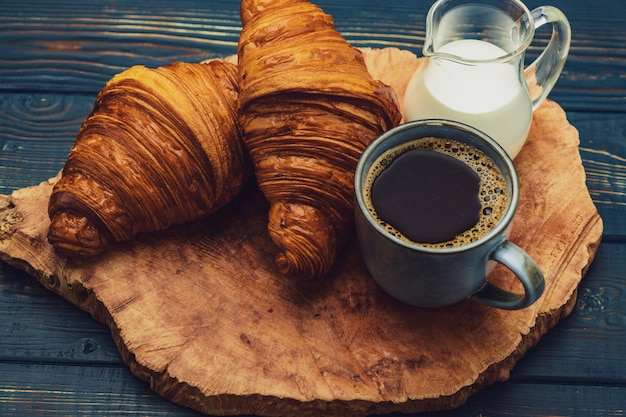 Кофе с круассаном и сливками на деревянной тарелке
