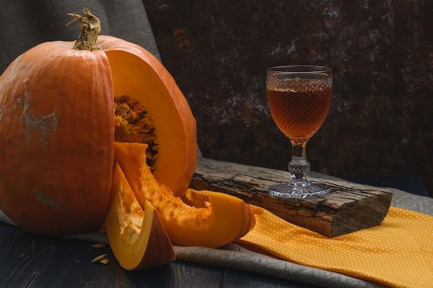 ワインのグラスと素朴なスタイルのテーブルの上のカボチャ