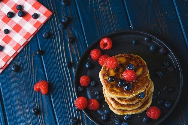 Блинчики с медом и ягодами на деревянном столе
